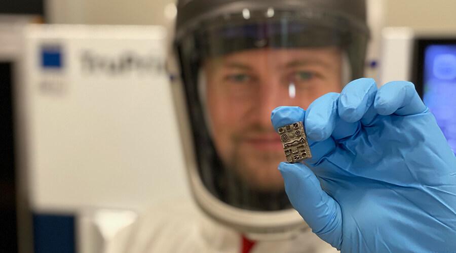 Clemens Maucher zeigt ein im LPBF-Verfahren (Laser Powder Bed Fusion) hergestelltes Testbauteil für die Mikrobearbeitung. | Quelle: IFW Stuttgart