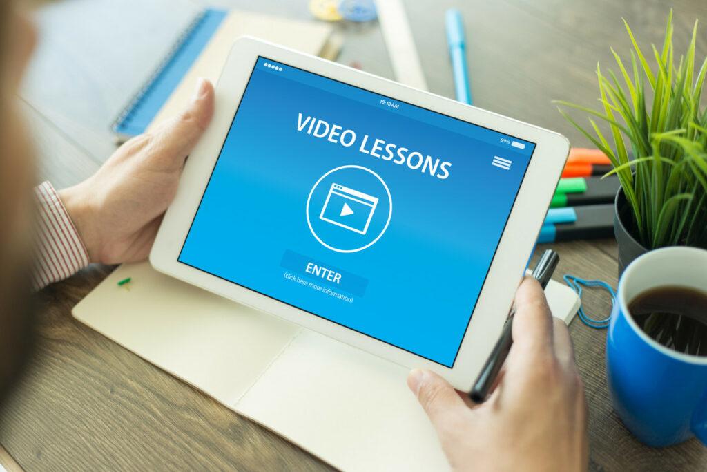 """Mann am Arbeitsplatz, der auf ein Tablet blickt auf dem steht """"Video Lessons"""", ein Play-Pfeil und """"ENTER""""."""