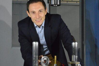 Robert Meißner, Projektmitarbeiter, an einer servo-machanischen Kaltfließpresse mit einem gebauten Zahnrad, Quelle: IFU Stuttgart